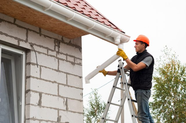 Worker installing Eugene Gutter standing on a ladder with safety hat on